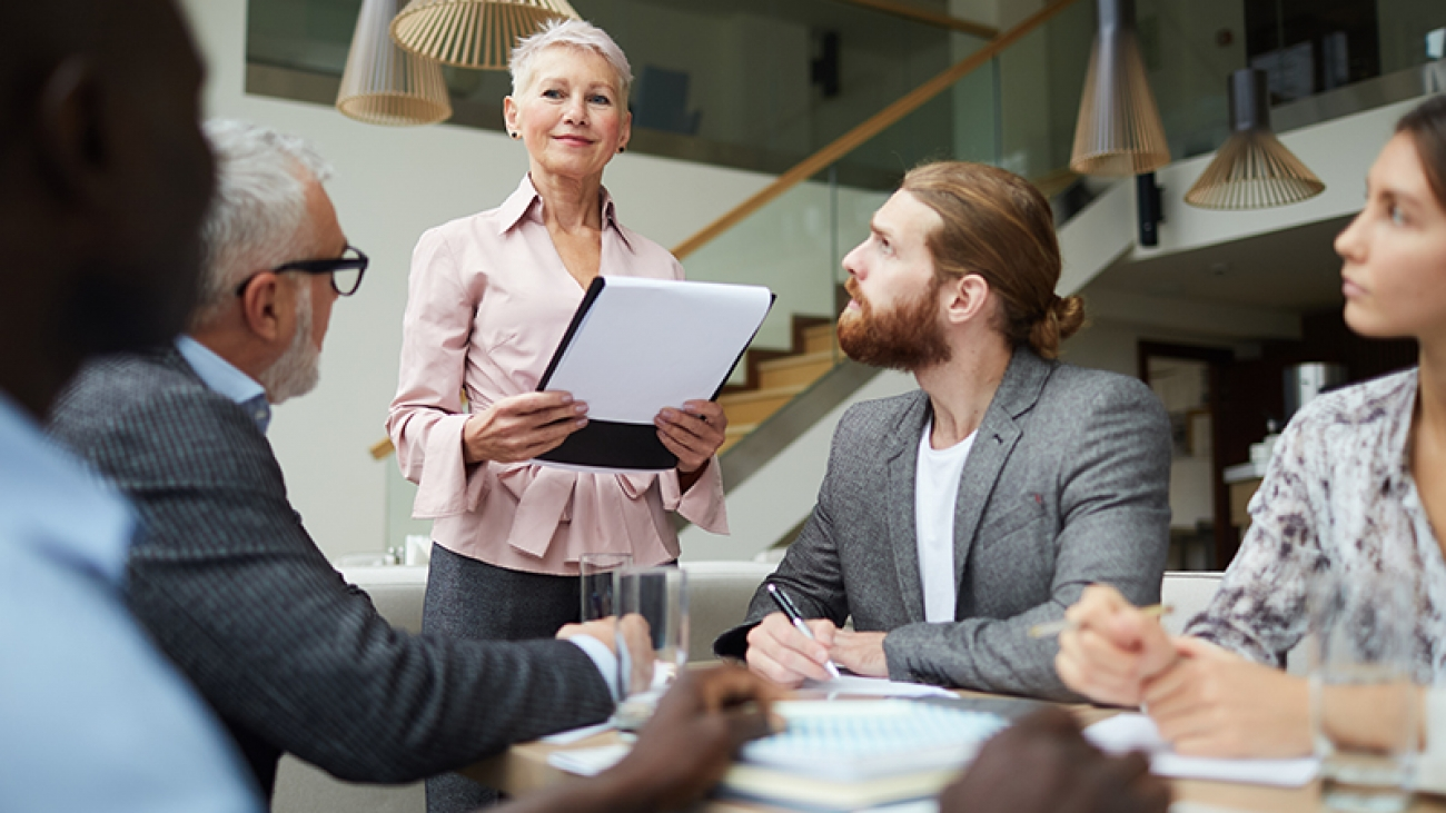 Portrait of modern senior businessman leading meeting with employees in office and holding clipboard, copy space