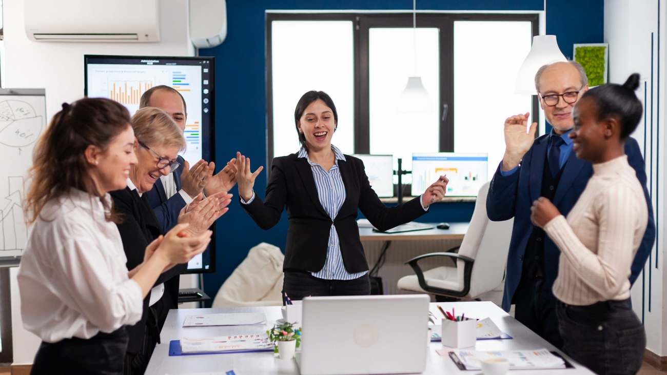 Motivated happy diverse business team people clapping celebrating success at corporate meeting. Multiethnical partners coworkers celebrate successful teamwork result at company briefing