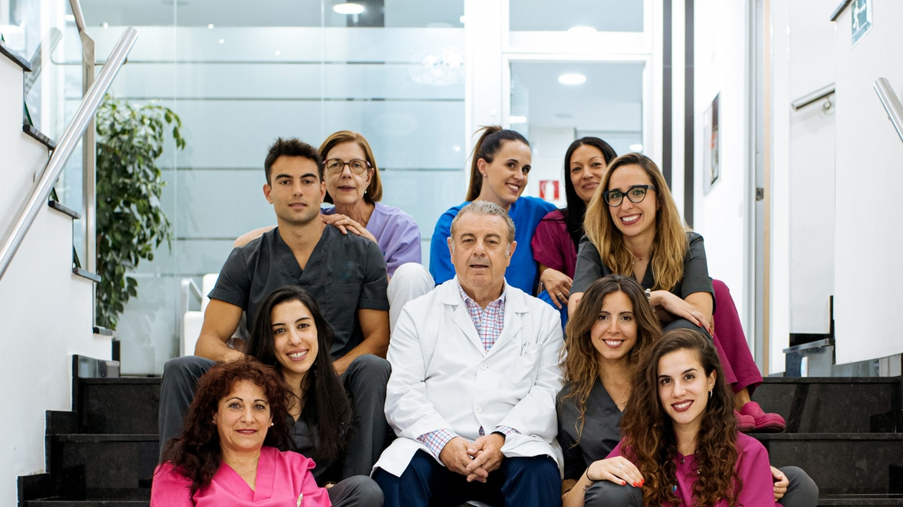 staff group of dental clinic nurse doctors colleagues portrait sitting and looking at camera
